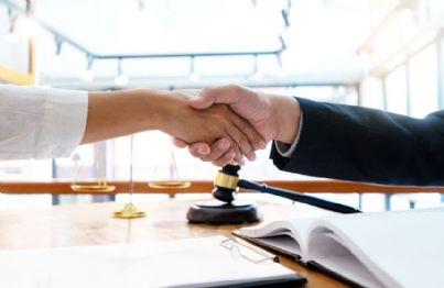 accordo e stretta di mano con bilancia e martello giudice