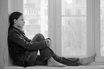 adolescente triste dietro la finestra