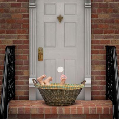 bimbo in una cesta sulla porta di casa concetto adozione