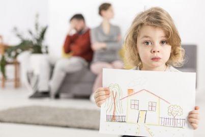bambina mostra disegno casa mentre genitori divorziati seduti sul divano