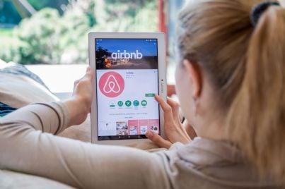 donna che cerca affitto breve su airbnb tramite tablet
