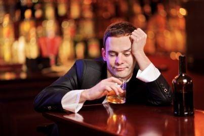 Uomo al bar che beve whisky