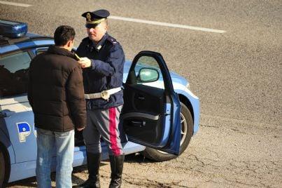 agente che fa alcoltest su un uomo alla guida