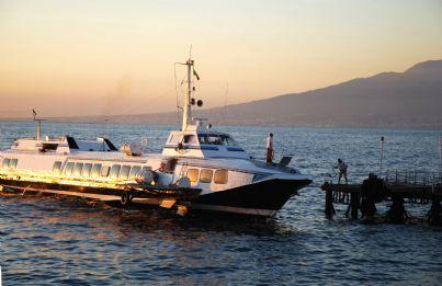 aliscafo che attracca al porto al tramonto