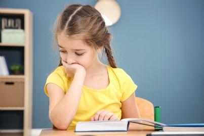 alunna preoccupata con davanti testo di scuola