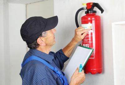 tecnico antincendio controlla estintore in condominio
