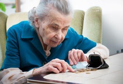 anziana che conta soldi della pensione