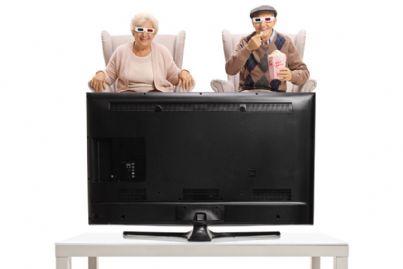 anziani guardano tv mangiando popcorn