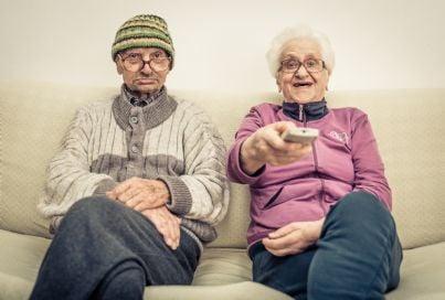 anziani guardano televisione spostando telecomando