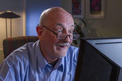 anziano pensionato che guarda sorpreso il computer
