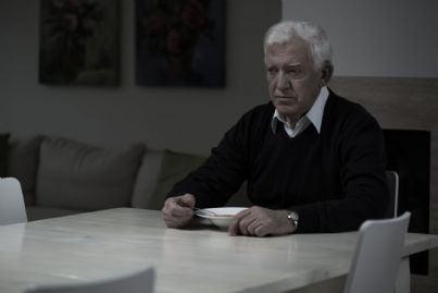 triste anziano al tavolo solitario