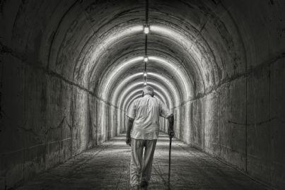 anziano solo con bastone si incammina verso un tunnel