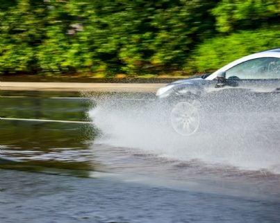 auto che fa aquaplaning su strada bagnata dalla pioggia