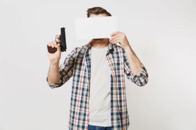 uomo con pistola e cartello bianco sul volto