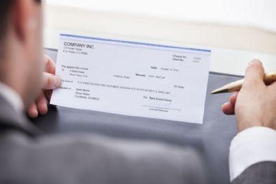 uomo che compila assegno