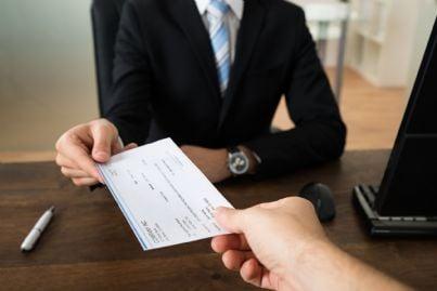mano di imprenditore che consegna assegno ad altra persona