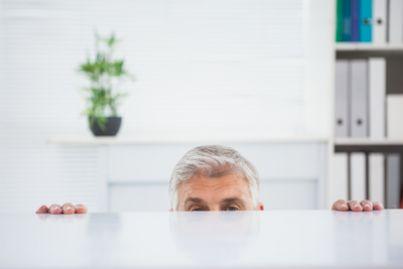 Uomo nascosto dietro una scrivania
