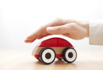 mano che protegge auto assicurata