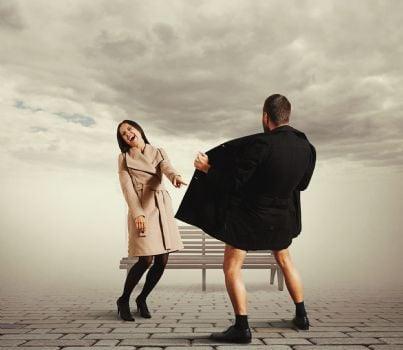 donna ride di fronte a maniaco impermeabile simboleggiante atti osceni