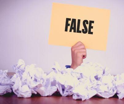 fogli di carta sparsi con cartello tenuto da una mano con scritto falso
