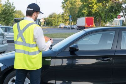 vigile che fa multa ad auto