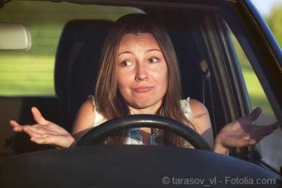 Donna al volante con mani alzate