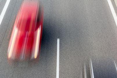 auto rossa che va molto veloce in strada