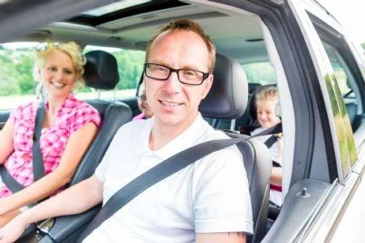 famiglia in auto che indossa cinture di sicurezza