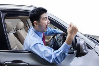 Automobilista arrabbiato che fa un gesto volgare con la mano
