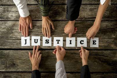 mani di avvocati che scrivono la parola giustizia