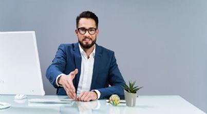 avvocato porge la mano seduto davanti al computer