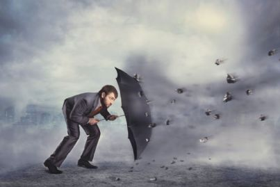 avvocato che si protegge con ombrello da caduta rocce