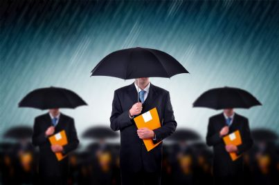 avvocati protetti da ombrelli con cartella assicurazione tra le mani