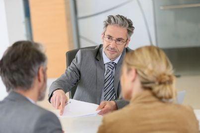 avvocato nel suo studio che mostra documento ai clienti