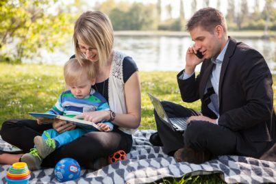 famiglia seduta al lago con padre che lavora al computer