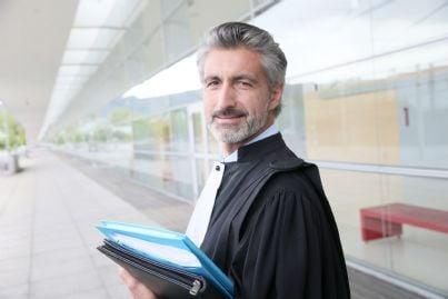 un giudice con fascicoli in mano di fronte a tribunale