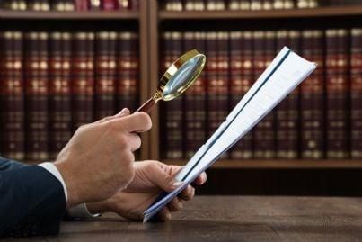avvocato guarda con lente un documento concetto di prova