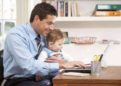 uomo con figlio in braccio al computer