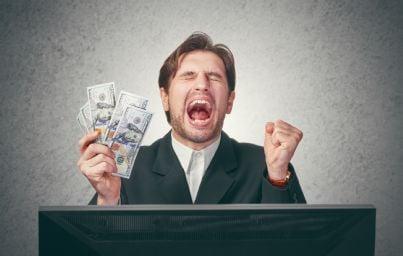 uomo affari con soldi davanti a computer