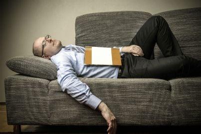 uomo stanco che dorme sul divano
