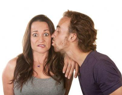 donna sorpresa mentre uomo la bacia sulla guancia