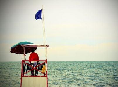 bagnino seduto nella postazione guarda spiaggia e mare