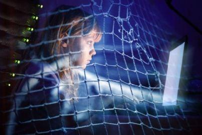 bambina al computer di notte circondata da una rete di dipendenza