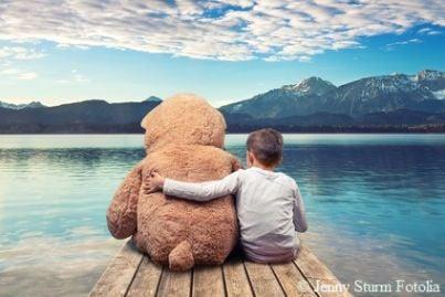 Bambina che abbraccia un grande orso di peluche seduta su un pontile di fronte a un lago