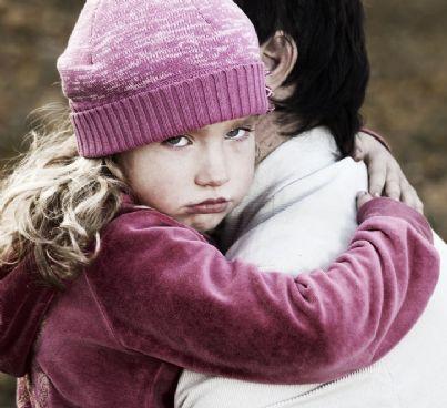bambina triste abbraccia il padre