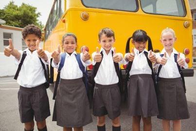 bambini in uniforme scolastica di fronte ad autobus
