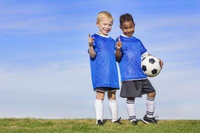 bambini in divisa che giocano a calcio