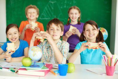 bambini che mangiano a scuola un panino