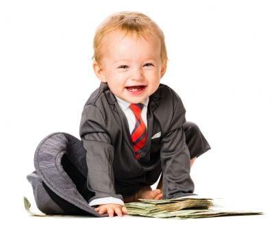 bambino con giacca e cravatta sorride di fronte ai soldi