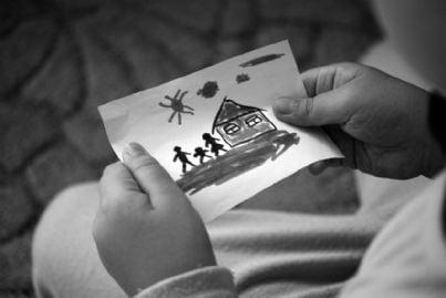 bambino con in mano disegno della famiglia